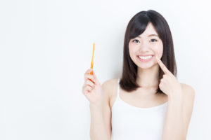 woman holding toothbrush pointing to teeth